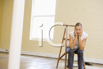 Royalty Free Photo of a Girl in an Empty Room Looking Bored