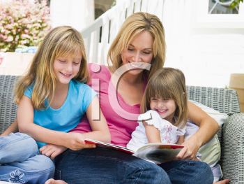 Royalty Free Photo of a Woman and Two Girls Reading Outside