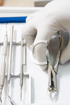 Royalty Free Photo of a Plastic Gloved Hand Reaching for Dental Tools