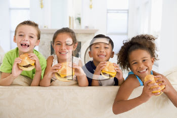 Royalty Free Photo of Four Children Eating Cheeseburgers in a Living Room