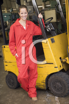 Royalty Free Photo of a Warehouse Worker Beside a Forklift