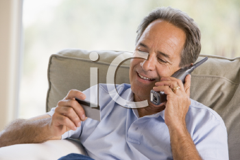 Royalty Free Photo of a Man on the Telephone Holding a Credit Card