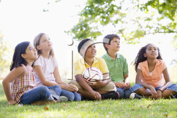 Royalty Free Photo of Five Children With a Soccer Ball Looking Up