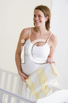 Royalty Free Photo of a Pregnant Woman Setting Up a Baby Crib