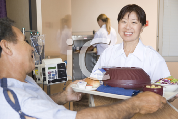 Royalty Free Photo of a Nurse Serving a Patient His Meal