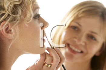 Royalty Free Photo of a Woman Applying Another Woman's Makeup
