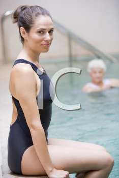 Royalty Free Photo of a Woman Sitting on the Edge of a Pool