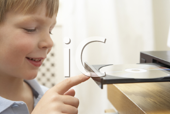Royalty Free Photo of a Child Loading a CD