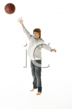 Young Boy Jumping With Basketball In Studio