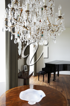 Room In Modern House With Chandelier And Grand Piano