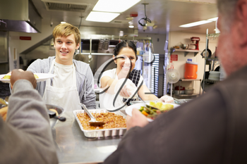 Staff Serving Food In Homeless Shelter Kitchen