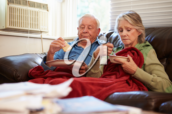 Senior Couple With Poor Diet Keeping Warm Under Blanket