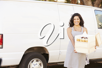 Female Baker Delivering Cakes Standing In Front Of Van