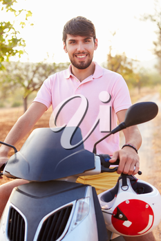 Young Man Riding Motor Scooter Along Country Road