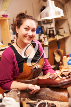 Woman shoemaker making shoes in a workshop