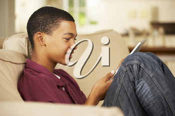 Teenage Boy Sitting On Sofa At Home Using Tablet Computer