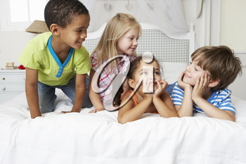 Four Children Playing On Bed Together