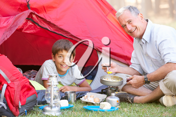 Grandfather And Grandson Cooking Breakfast On Camping Holiday