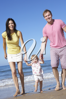 Family With Young Daughter Walking Along Beach Together