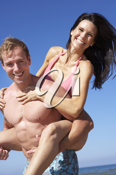 Couple Having Fun On Beach Holiday Together
