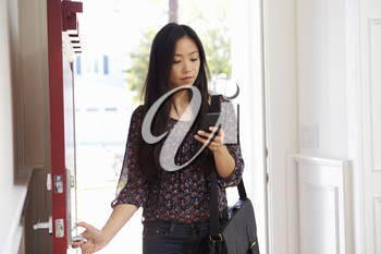 Woman Opening Front Door Whilst Checking Mobile Phone