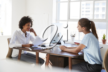 Two young women talking across their  desks in an office