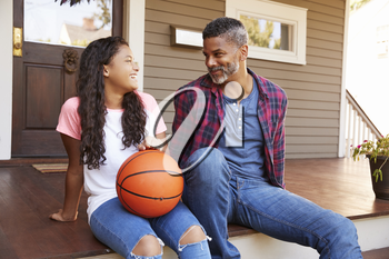 Father And Daughter Discussing Basketball On Porch Of Home