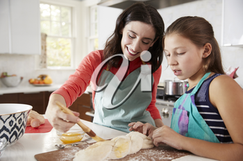 Jewish mother and daughter glazing dough for challah bread