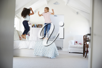 Happy young female friends jumping on the bed in a bedroom