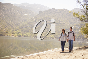 Senior couple hold hands hiking by mountain lake, front view