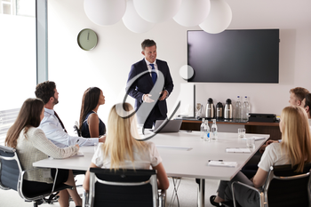 Mature Businessman Addressing Group Meeting Around Table At Graduate Recruitment Assessment Day