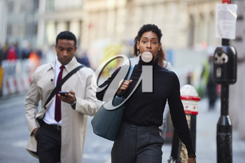 Young black woman walking in a London street carrying handbag, front view