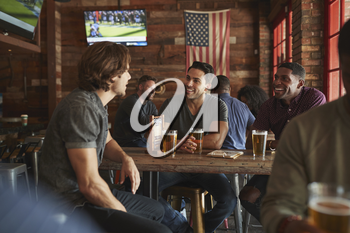 Group Of Male Friends Meeting And Drinking Beer In Sports Bar Together