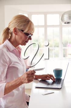 Mature Woman At Home Looking Up Information About Medication Online Using Laptop