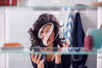 View Through Bathroom Cabinet Of Frustrated Mature Businesswoman Checking Message On Mobile Phone