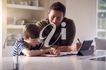Father Helping Son With Homework Sitting At Kitchen Counter Using Digital Tablet Together
