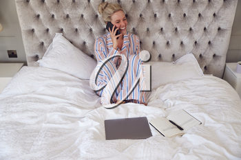 Businesswoman In Pyjamas Sitting On Bed Making Call On Mobile Phone Working From Home