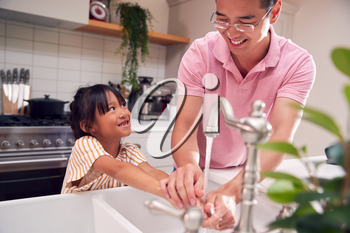 Asian Father Helping Daughter To Wash Hands With Soap At Home To Stop Infection In Health Pandemic
