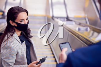 Businessman And Businesswoman Riding Escalator At Railway Station Wearing PPE Face Mask In Pandemic