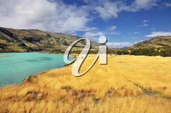 National Park Torres del Paine in southern Chile, in Patagonia. The sharp strong wind bends the yellowed grass. Emerald Lake is covered by waves