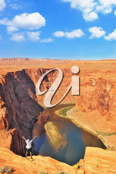 An enthusiastic traveler raised his hands on a steep and dangerous shore of the Colorado River. The well-known river Colorado is picturesquely bent in the Horseshoe.