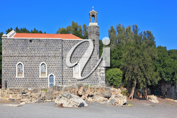 One of the oldest churches in the Sea of Galilee. Stone wall of gray stone on a smooth slope to the lake water