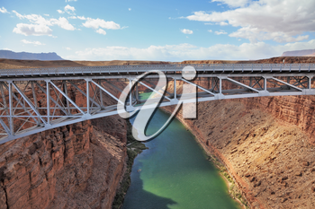 The easy metal bridge through the river Colorado in abrupt coast of desert from red sandstone