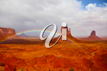 Red stone desert Navajo, USA. Isolated rocks - mitts intersect with the beautiful rainbow