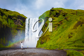 Grand waterfall with rainbow in the water mist Skogafoss. Elderly woman performs asana tree of hatha yoga before falling water