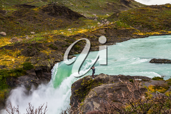 Travel to Patagonia. A lonely woman photographer on a cliff near the powerful waterfall Salto Grande in Torres del Paine. Concept of active and extreme tourism