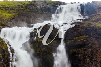 Rainy and cold July in Iceland. Powerful streams of cascade falls with a roar fall in a chasm. Concept of active and extreme tourism