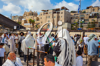 JERUSALEM, ISRAEL - OCTOBER 12, 2014:  The area in front of Western Wall of Temple filled with people.  Morning autumn Sukkot, Blessing of the Kohanim. The Jews of tallit hold four ritual plants