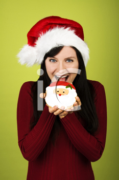 Royalty Free Photo of a Woman in a Santa Hat Eating a Santa Cookie