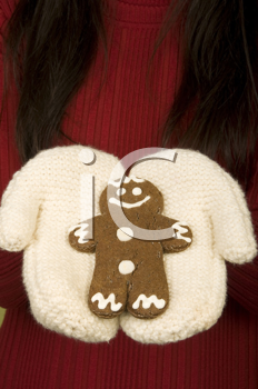 Royalty Free Photo of Mittens Holding a Gingerbread Man